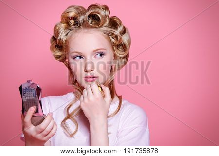 Portrait of a pretty girl teenager with curlers in her blonde hair painting lips with lipstick. Teen style, fashionable teen girl. Cosmetics and make-up.