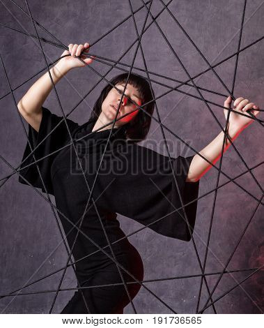 beautiful fashionable lady wearing a gothic black dress poses on a grey background. close-up portrait
