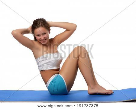 The beautiful sports girl does exercises on a floor-mat on a white background. Fitness.