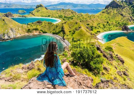 Rear view of a young woman enjoying the awesome view of Padar Island while sitting on the top of a volcanic mountain, during summer vacation in Indonesia poster
