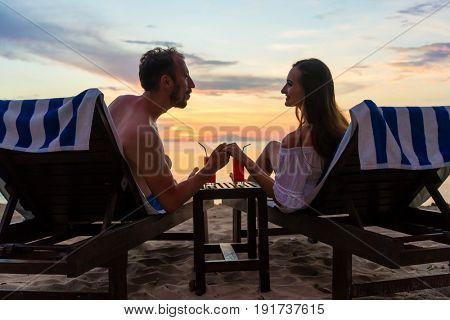 Rear view of a young couple holding hands while watching together the sunset on the dreamy beach of an exotic island, during summer vacation or honeymoon