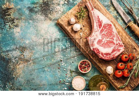Raw tomahawk beef steak with ingredients for grilling: seasoning, fresh rosemary and olive oil on cutting board, top view
