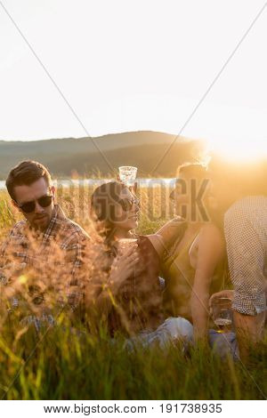 Friends enjoying evening mood of summer day sitting in high grass with drinks and guitar music
