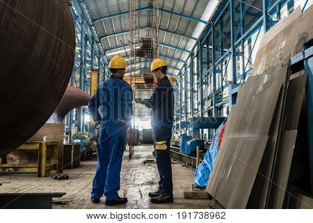 Two workers wearing yellow hard hat and blue uniform in the interior of an industrial hall