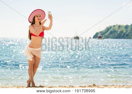 Beautiful young woman blowing a kiss while sharing on social media a selfie picture or a live video during summer vacation in Flores Island, Indonesia