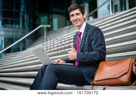 Portrait of successful young businessman showing thumb up while working on laptop outdoors