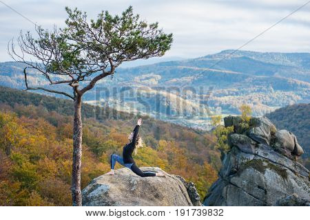 Sporty Fit Girl Is Practicing Yoga And Doing Asana Virabhadrasana 1 On The Top Of The Mountain Near
