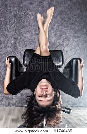 beautiful fashionable lady wearing a gothic black dress with high collar, poses upside down on a leather armchair on a grey background
