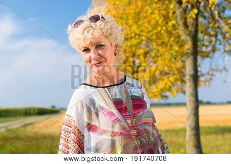 Portrait of a serene senior woman looking at camera while enjoying the retirement outdoors in a sunny day in the countryside