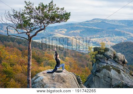 Sporty Young Woman Is Practicing Yoga And Doing Asana Virabhadrasana 1 On The Top Of The Mountain Ne