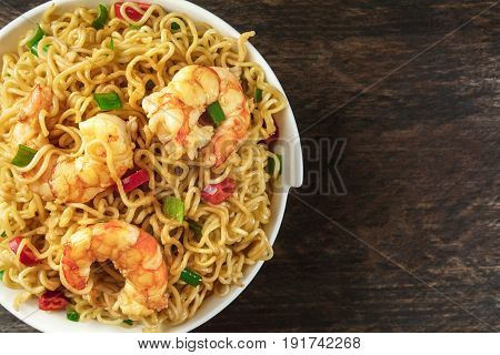 A closeup of a bowl of instant Chinese noodles with green onions, red hot chilli peppers, and shrimps, shot from above on a dark rustic texture with a place for text