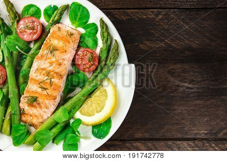 A closeup of a plate of grilled salmon with green asparagus, cherry tomatoes, corn salad, and a slice of lemon, a healthy diet dish shot from above on a rustic texture with a place for text