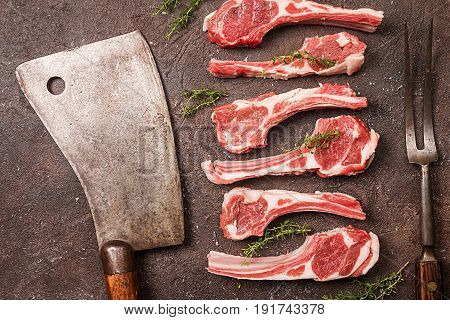 Raw lamb chops with salt, pepper and herbs over black brown background with Meat cleaver and fork near. Top view.