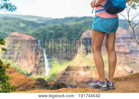 HIking hiker girl at Waimea Canyon Kauai looking at Waipoo falls Hawaii waterfall. Kauai travel.