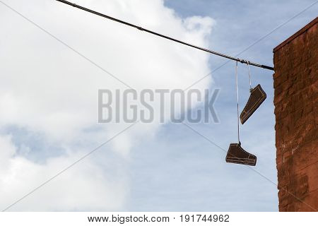Two cardboard gumshoes in the blue sky with white clouds