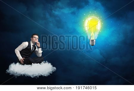 Caucasian businessman sitting on a white fluffy cloud lookind and wondering at a big, shiny, glowing yellow lightbulb