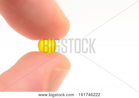 Contraceptive tablet without package, sandwiched two fingers against a light background. Preparations of medical purpose.