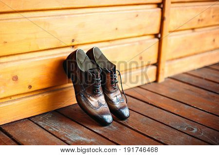 Brown leather man shoes near wooden wall. Man casual vintage accessories.
