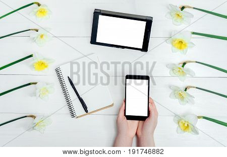 Top View On Table With Narcissus, Empty Diary, Tablet And Girl's Hands With Cell Phone With White Sc