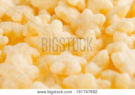 Yellow stars corn flakes closeup cereals texture.
