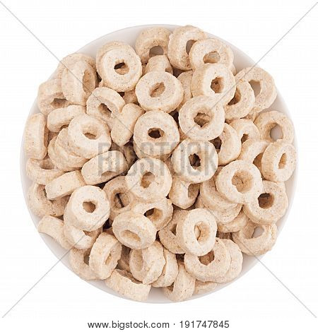 Beige rings corn flakes in white bowl isolated top view. Cereals.