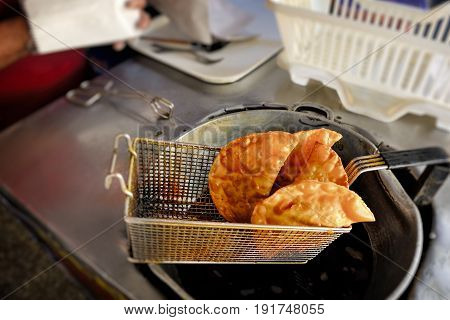 Close-Up Of Fried Empanadas. Chef making empanadas (pastel patepirozhki) in commercial kitchen. Traditional Latin American food. Fast food.