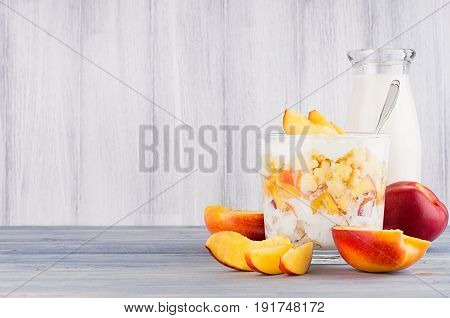 Healthy breakfast with corn flakes slice peach and milk bottle on white wood board. Decorative border with copy space.