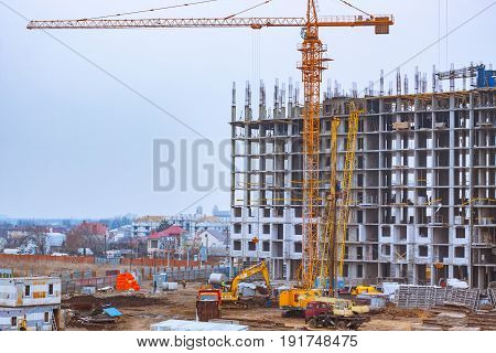 Building under construction and tower crane, group of construction building tenement apartment houses