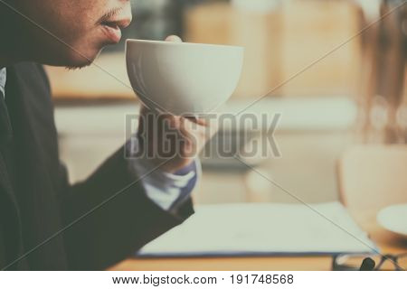 cup of coffee on old wooden desk. Simple workspace or coffee break in morning/ selective focus