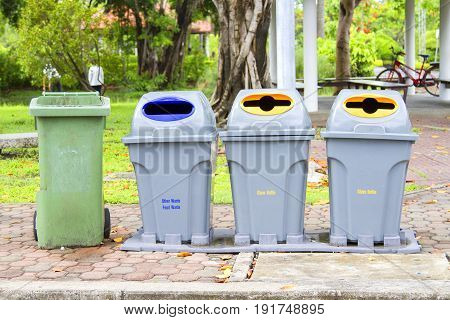 Four bins are on the sidewalk in the park.