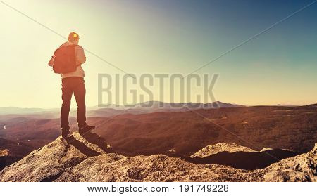 Man Standing At The Edge Of A Cliff Overlooking The Mountains