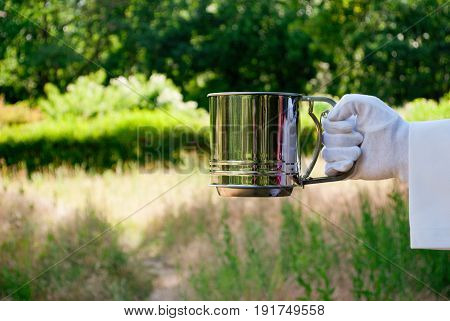 The hand of the waiter in a white glove and with a white napkin holds an empty metal container for sifting flour sieve on a blurred background of nature green bushes and trees
