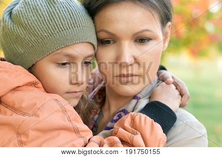 Sad mother hugging her little daughter outdoors