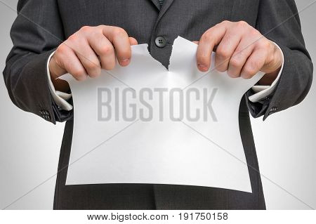 Businessman tearing white blank paper - business idea concept