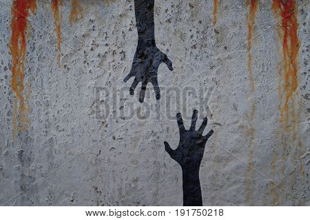 Zombie hands silhouette in shadow on concrete wall and blood background with copy space for text or image. Zombie and halloween theme with corpse hands in cemetery.