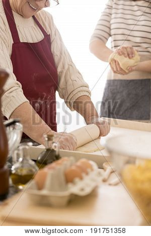 Happy senior woman rolling dough for pasta