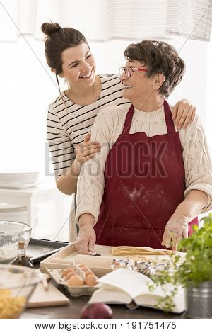 Woman embracing her grandma while cooking together