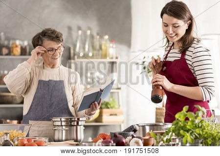 Woman cooking and her grandmother reading recipe from cookbook