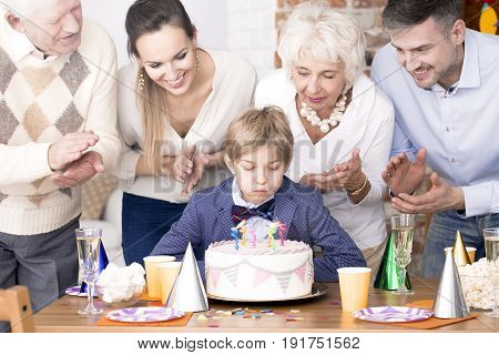 Little boy blowing out candles on birthday cake and his family watching him