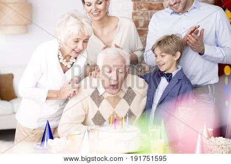 Grandpa blowing out candles at his birthday cake and his family watching him