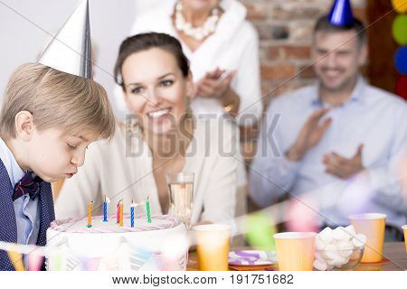 Birthday boy blowing candles on a cake and his family watching him
