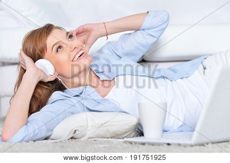 Beautiful young woman lying on floor with white carpet in front of laptop