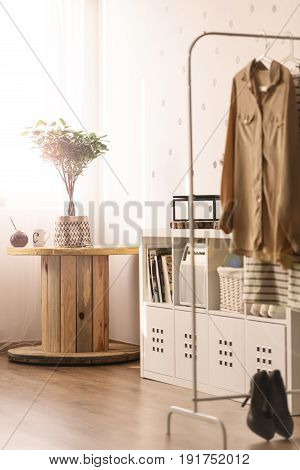 White room with cable spool table bookshelf and clothes rack
