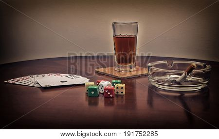 Glass of alcohol, cards, dice and ashtray with cigarette on the brown table. Filtered photo with toned and selective focus on the glass of alcohol drink.