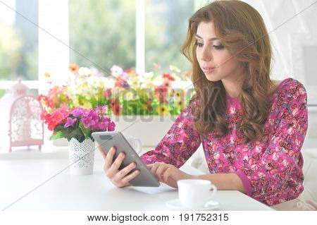 Beautiful curly young woman sitting at kitchen table with digital tablet