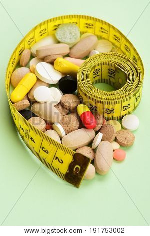 Health And Diet Concept: Yellow Measuring Tape And Various Pills