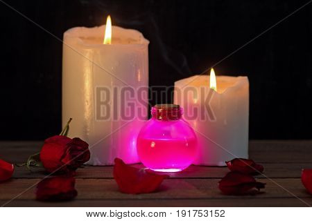 magical pink love potion and canles and dry roses