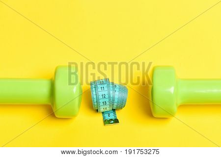 Roll Of Flexible Ruler In Turquoise Color Lies Between Dumbbells