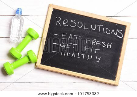 Checklist for fitness. Sign with resolutions for proper lifestyle written on blackboard: eat fresh get fit and healthy on white wooden background near green dumbbells and water bottle. To do list