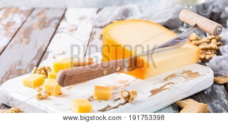 Delicious dutch gouda cheese with cheese blocks, crackers, walnuts and special knife on old wooden table.